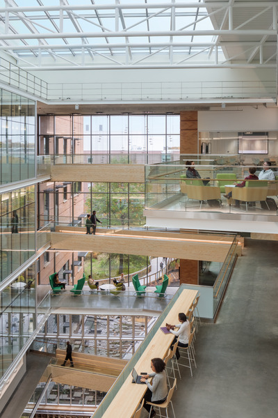 Light-filled atrium with exposed concrete and steel structure and wood finishes.