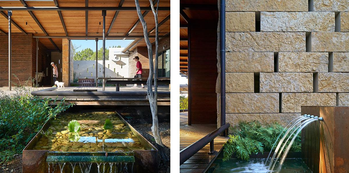 Wood and steel canopy over an outdoor wood deck surrounded by stone walls and water features.