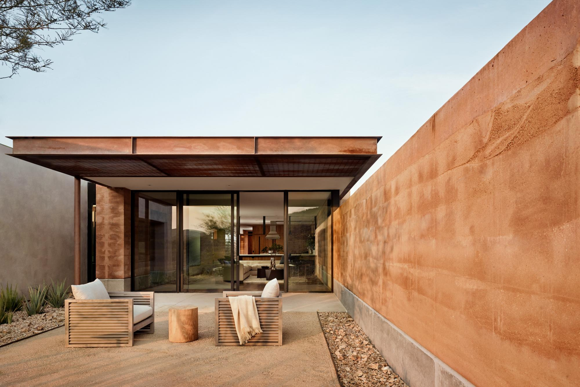The rammed earth walls create outstretched wings that frame a private landscape while blocking the intense west exposure and northern winter winds.