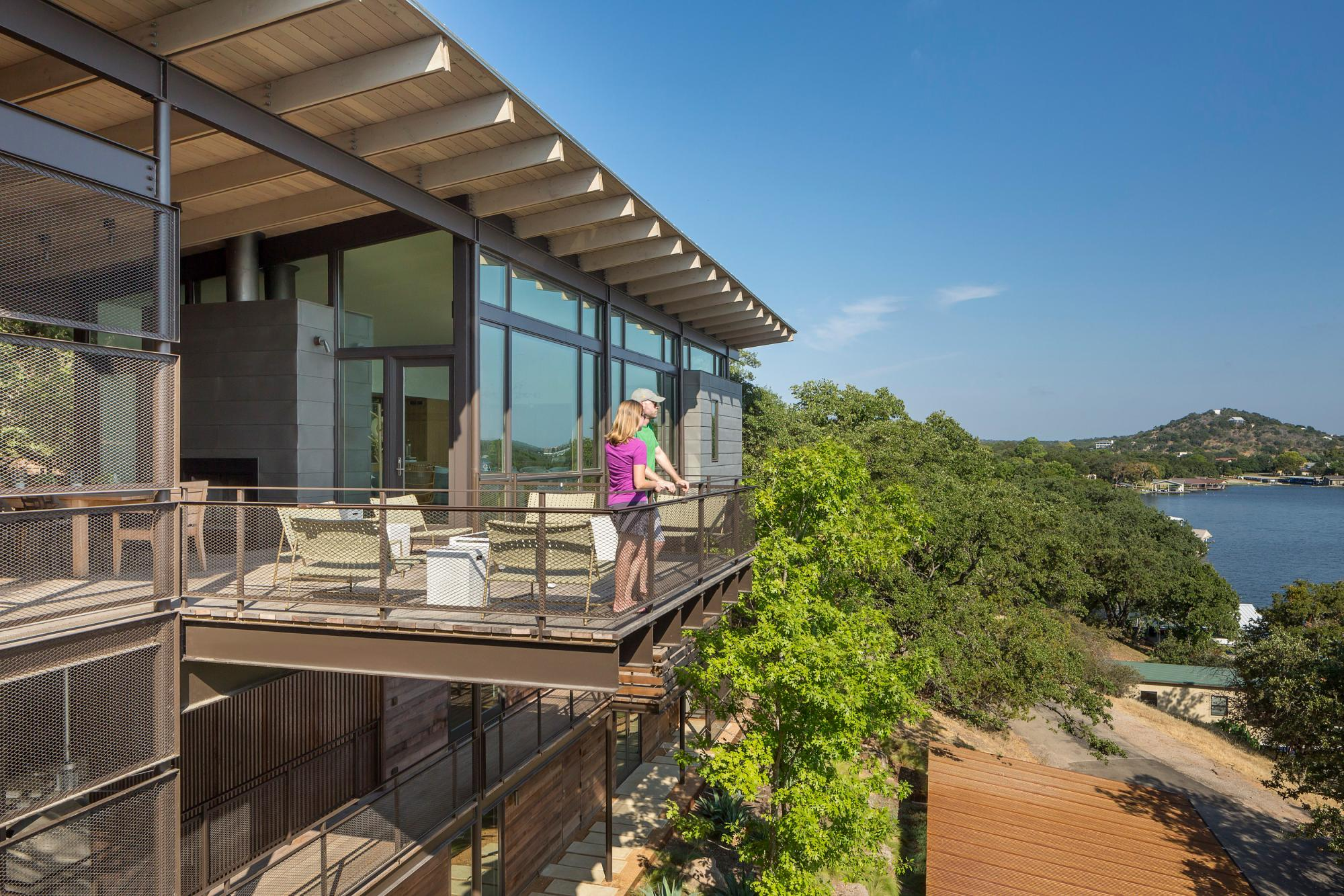 The long, narrow three-story residence dramatically culminates at the top floor, set just above the tree line and providing a nearly 180-degree view of the lake beyond. The third floor north-facing glazed wall offers unobstructed views of the lake,