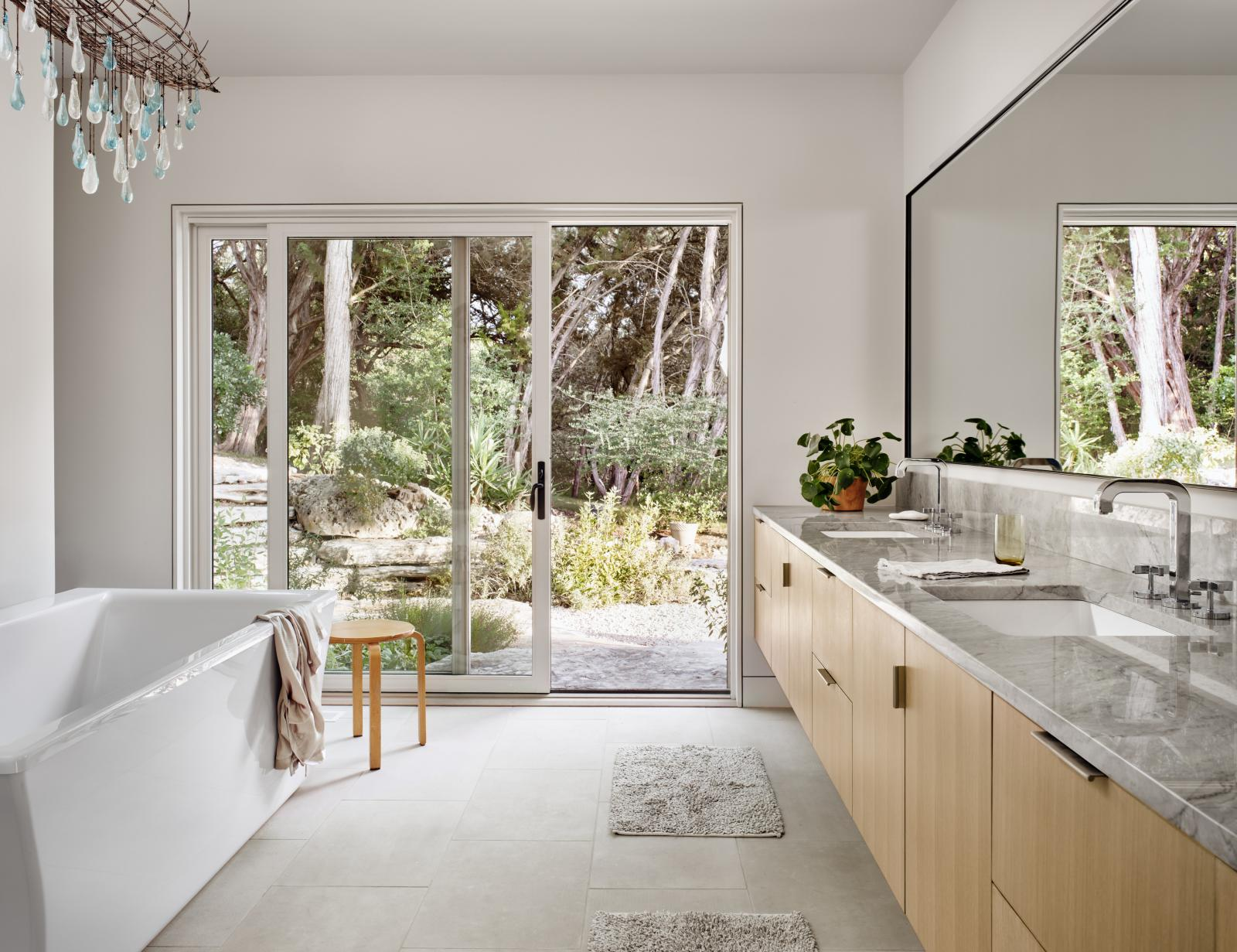 Interior master bathroom connects through a sliding glass door to outdoor landscape