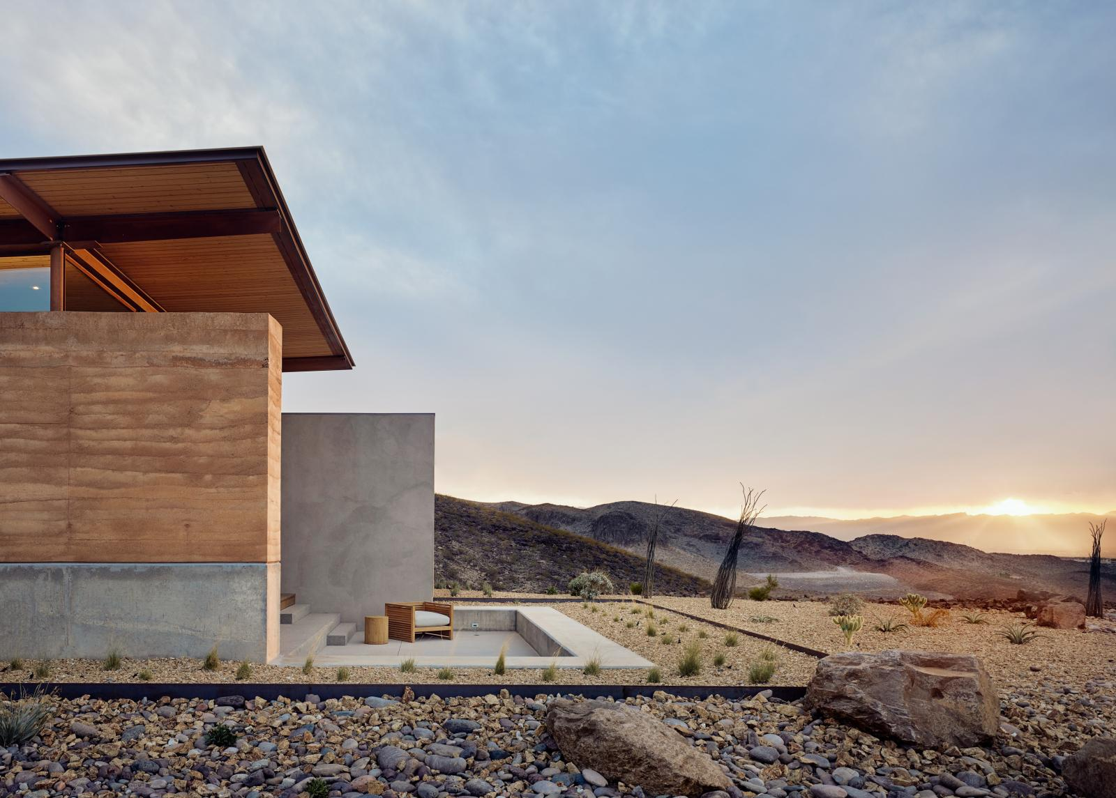 The rammed earth textures, colors and materials blend seamlessly with the surrounding desert.