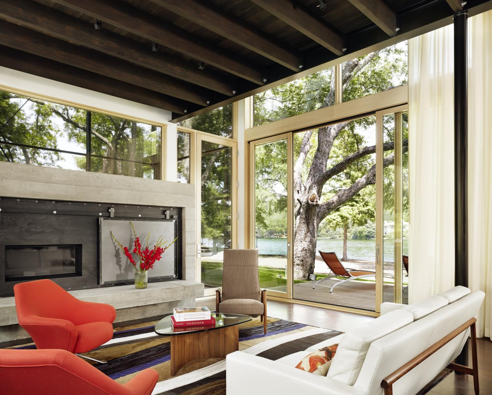 Hog Pen Creek Residence was envisioned by its owners as a place that evokes the playfulness of summer on the lake. Interior image looking across the living room seating area with views to outside porch and lake.